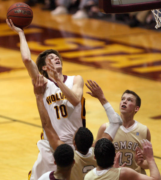 Northern State University's Michael Emge, left, goes up with a shot as Southwest Minnesota State University's Tramel Barnes, center defends and Jordan Miller, right, looks on during the first half of Friday night's game at Wachs Arena.