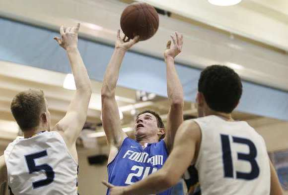 Fountain Valley's Josh Armstrong, who scored a career-high 38 points, takes a shot over Marina's Mitchell Barnes (5) and Derek Mallard (13) during a Sunset League game on Friday.