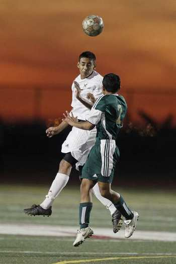 Estancia's Abraham Cortez goes up for a header against Saddleback's Mario Ramirez during an Orange Coast League match.