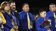 The parents of Martin Alberto Garza listen to their son's football coach speak.