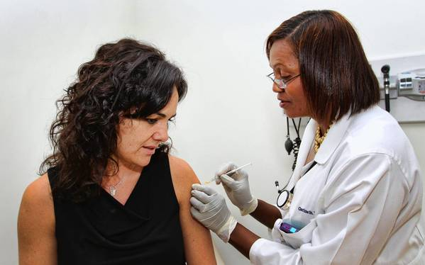 Lora Thompson, left gets a flu shot from Carline St.Vil-Joseph, ARNP at the ADT clinic in Boca Raton.