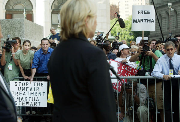 Martha Stewart supporters look on as she speaks to the media outside Federal Court after her sentencing hearing for insider trading in 2004. Stewart was sentenced to five months in federal prison, two years probation and $30,000 in fines.