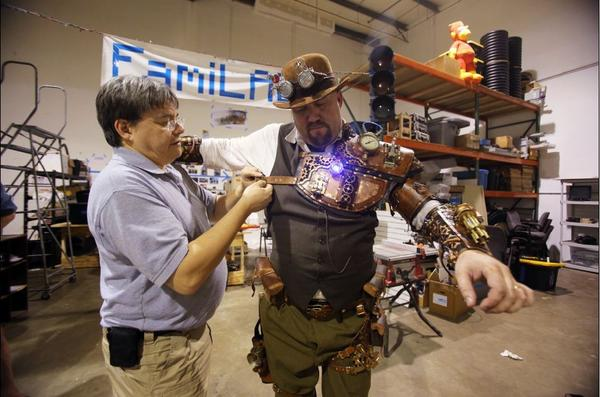 Mike Bakula helps R.J. Foster get in his Steampunk-style costume. It borrows elements from the Steam Age and reinvents them using high-tech and fantasy motifs.