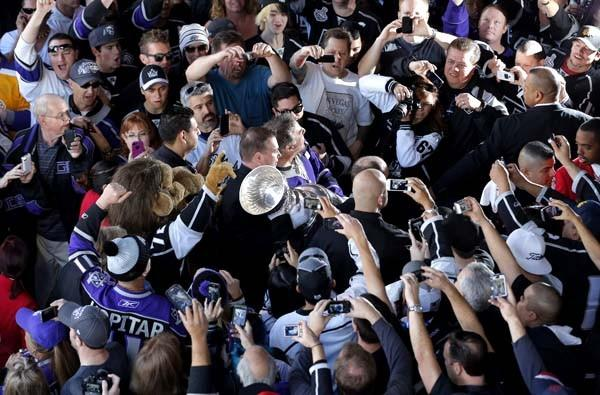 Kings fans cheer as they take pictures of the Stanley Cup outside Staples Center on Saturday before the season opener.