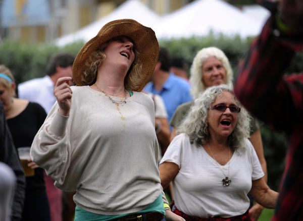 Music lovers like Katie Allen of New Rochelle, New York dance to the music of Big Sam's Funky Nation at The Sunshine Blues Festival Saturday at the Mizner Park Amphitheater in Boca Raton.