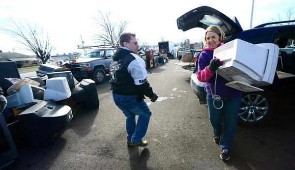 Wendy Gordon Rodriguez of Slatington, general manager of Responsible Recycling Services of Kutztown, right, takes electronic goods to be recycled from a person dropping them off Saturday. Saturday was electronics recycling day at Northwestern Lehigh High School, sponsored by the school's chapter of SADD (Students Against Destructive Decisions).