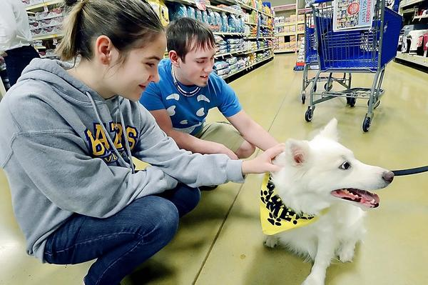 Courtney Myers and Curtis Zellers play with Reno, an American Eskimo that is up for adoption with the Hounds of Prison Education program.