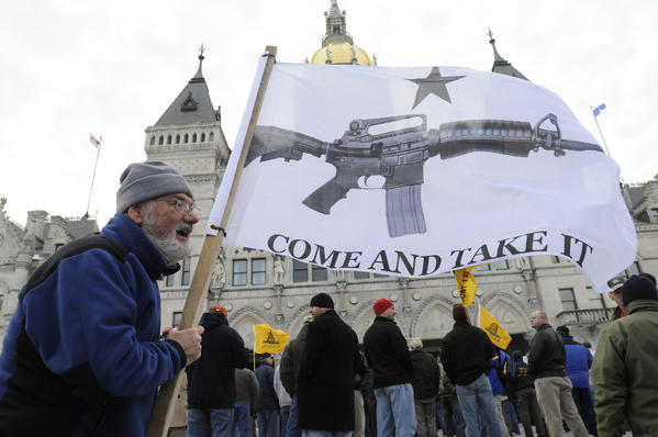 Gregory Majewski of Montville holds a flag in front of the State Capitol Saturday afternoon.