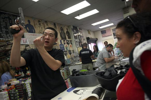 Joseph Im of the Los Angeles Gun Club shows the workings of a revolver to Tamara Vravis before she goes into the shooting range. Business was brisk Saturday, but according to Im, the club is busy every weekend.