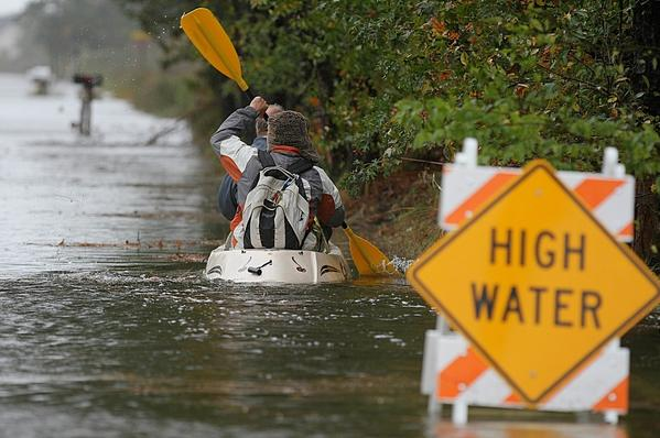 Hampton Roads faces challenges with rising sea levels, flooding, hotter temperatures, and more. Peninsula residents kayak through the flooding during Hurricane Sandy on Oct. 28, 2012.