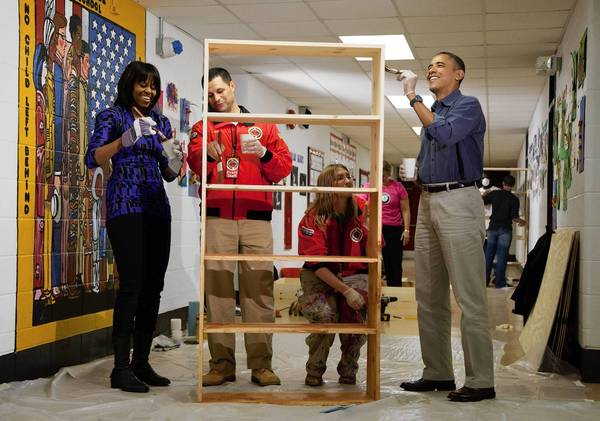 President Obama and First Lady Michelle Obama help stain a bookshelf at Burrville Elementary School in Washington. Joining the Obamas are Jeff Franco and Sheri Fisher of City Year, an AmeriCorps program.