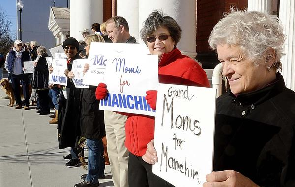 Donn Marshall, Tamara Cooper, both of Martinsburg and Martha Hanley of Gerrardstown holds signs in support of Sen Joe Manchin.  The Moms for Manchin group gathered in front of the Berkeley County Courthouse on Saturday.