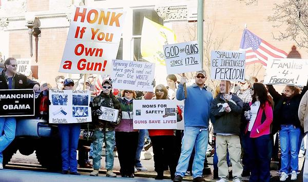 People hold signs showing their views on the second amendment at a West Virginia Citizens Defense League Rally in Martinsburg on Saturday.