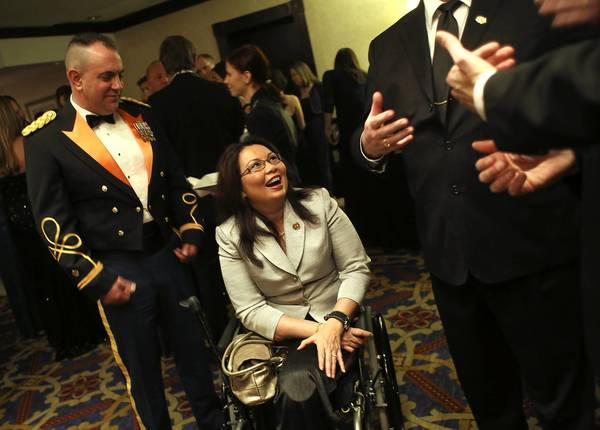 U.S. Rep. Tammy Duckworth, center, and her husband, Major Bryan Bowlsbey, U.S. Army National Guard, chat during cocktail hour before the Illinois Inaugural Gala in Washington D.C.