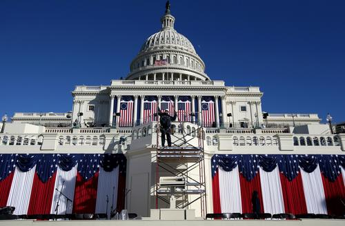 A worker removes scaffolding at the Capitol as preparations continued for Monday's ceremonies, expected to draw more than a half-million people.