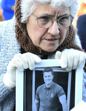 Mary Cardona holds a photo of Huell Howser as she and hundreds gathered Tuesday to celebrate and remember the life of the television host at Griffith Observatory.