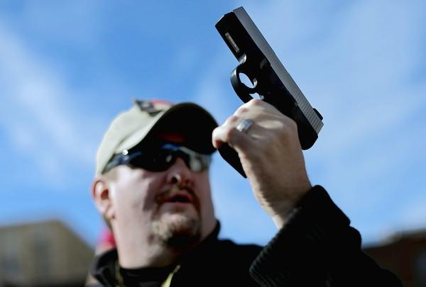 Derek Ringley shows a pistol being auctioned at an event organized to compete with First Presbyterian Church of Dallas' gun buyback.
