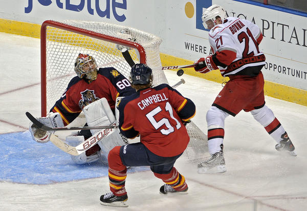 Florida Panthers goalie Jose Theodore and Brian Campbell keep Carolina Hurricanes Drayson Bowman from scoring during the third period.