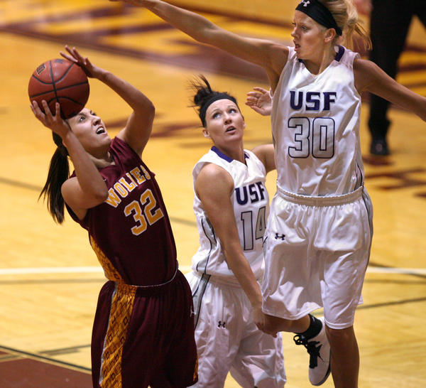 Northern State University's Alison Kusler, left, tries to shoot as University of Sioux Falls' Teagan Molden, right, and Jaicee Ulmer (14) defend during the first half of Saturday night's game at Wachs Arena. Northern State defended home court one