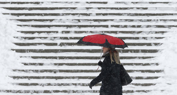 A woman shelters under an umbrella as she walks past snow-covered stairs at the Tuilerie gardens in Paris.