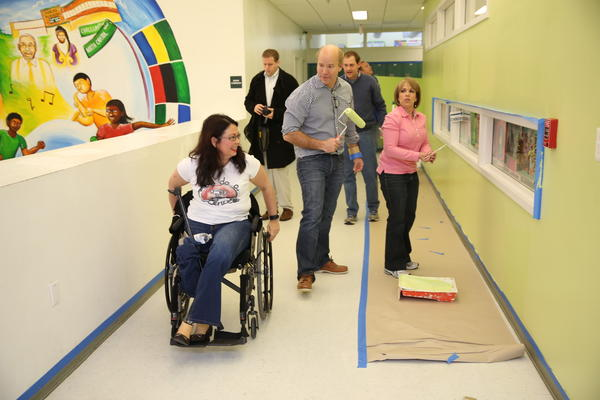 U.S. Rep. Tammy Duckworth of Illinois, left, slips past U.S. Rep. John Delaney, a fellow freshman Democrat, from Maryland, as they volunteer on Saturday at Ideal Academy Public Charter School in Washington D.C. as part of the National Day of Service. The events are leading up to the Monday inauguration of President Barack Obama.