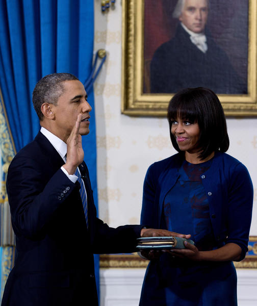 U.S President Barack Obama takes the oath of office as first lady Michelle Obama holds the bible in the Blue Room of the White House January 20, 2013 in Washington, DC.