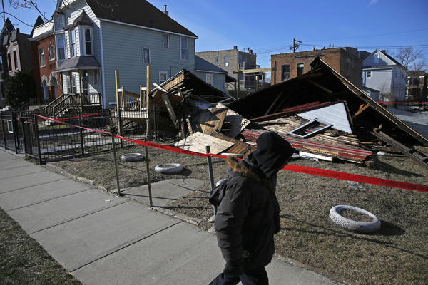 A pedestrian walks by a collapsed vacant house in the 6300 block of South Evans Avenue in Chicago today. No one was injured when the house collapsed Saturday night in the Grand Crossing neighborhood on the South Side, authorities said. By interviewing neighbors and using body-sensing technology, firefighters determined the home had been unoccupied when it collapsed.