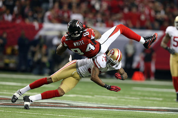 Atlanta Falcons wide receiver Roddy White (84) is hit as he makes a catch by San Francisco 49ers free safety Dashon Goldson (38) during the first quarter of the NFC Championship game at the Georgia Dome.