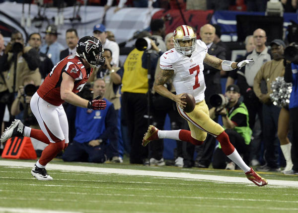 49ers quarterback Colin Kaepernick carries the ball past Falcons defensive end Kroy Biermann during the second quarter.