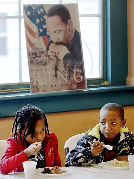Keiora Williams, left, and Jokari Barnette eat Sunday during a potluck dinner at Memorial Recreation Center Inc. in Hagerstown.