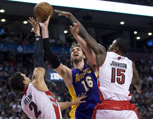 Lakers power forward Pau Gasol has his shot challenged by Raptors center Amir Johnson and forward Landy Fields in the second half.