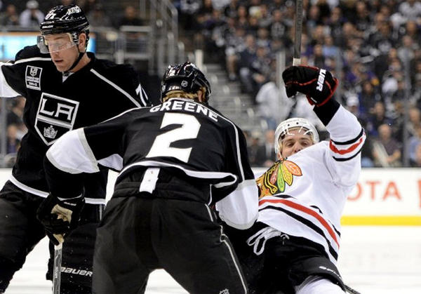 Kings' Matt Greene checks the Blackhawks' Patrick Sharp