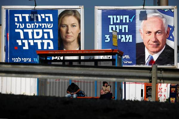 People wait at a bus stop near billboards picturing politicians Tzipi Livni, left, and Benjamin Netanyahu in Tel Aviv, Israel.