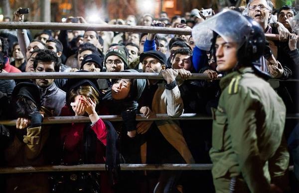 Onlookers watch the execution of Alireza Mafiha, 20, and Mohamad Ali Sorouri, 23, in Tehran. The two men were convicted of robbing a man while brandishing a dagger.