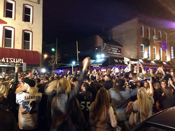 People gather on S. Charles Street in Federal Hill after the Ravens' victory over the Patriots.