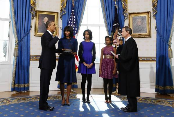 President Obama, with First Lady Michelle Obama and their children Malia and Sasha looking on, takes the oath of office. It was administered by Chief Justice John G. Roberts Jr.