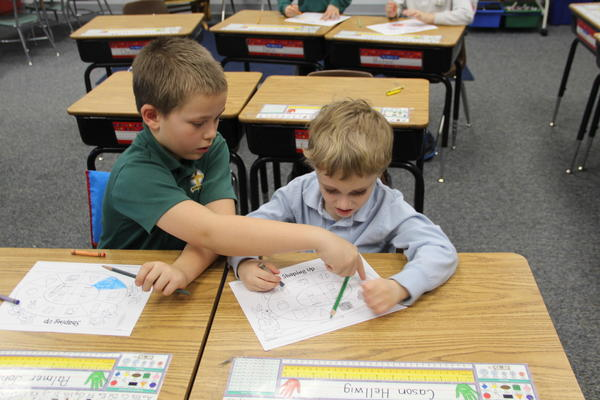 First-grader Landon Zikmund helps kindergartner Lane Homel with a math activity at Roncalli Primary School. Students from different grades get together once a week to learn additional math lessons together.