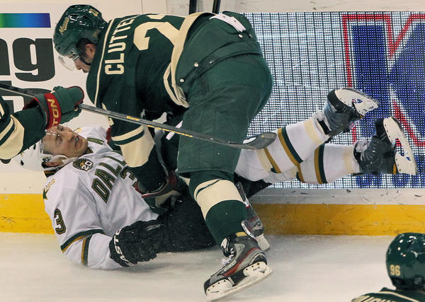 Minnesota Wild's Cal Clutterbuck checks Dallas Stars Stephane Robidas in first-period action at the Xcel Energy Center on Sunday in St. Paul, Minn.