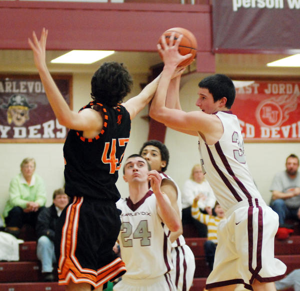 Charlevoix's Zach Hankins (right) battles Harbor Springs' Neal Zoerhof for a rebound during Friday's Lake Michigan Conference contest at the Charlevoix High School gym. The Rayders defeated the Rams, 60-50.