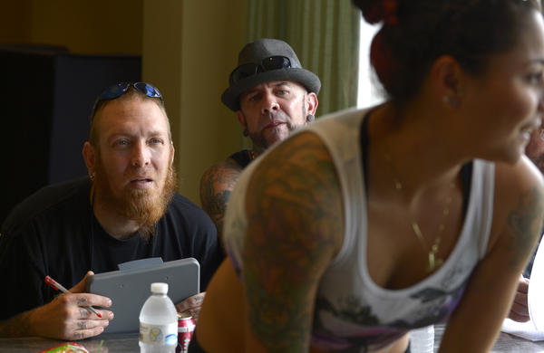 Brian Baker, left, and Scott Eastin judge the tattoo of Nani Berrios, right, of Atlanta, Ga., during the contest portion of the 18th Annual International MARKED FOR LIFE Female Tattoo Artist Expo in Orlando, Fla., Sunday, Jan. 20, 2012.
