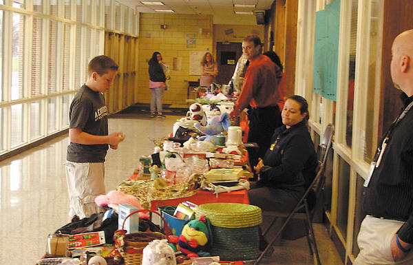 E. Russell Hicks Middle School student Nathan Wilson, left, shops for items as teachers and staff help.
