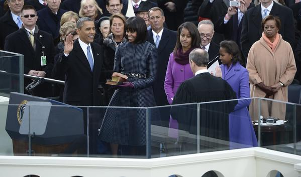 President Barack Obama places his hand on a bible held by Michelle Obama as he is ceremonially sworn in for a second term by Chief Justice John Roberts, right.