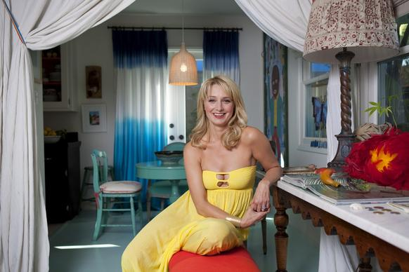 "Katherine LaNasa sits in her entryway, which opens onto a dining nook. She separated the two areas with heavy vintage English sheets that she found at a flea market and turned into floor-to-ceiling drapes, which soften the hard edges of the space. ""It makes it more inviting,"" she said. Behind her: an Ikea pendant lamp and dip-dye curtains, which she sewed from sheets, then dyed."