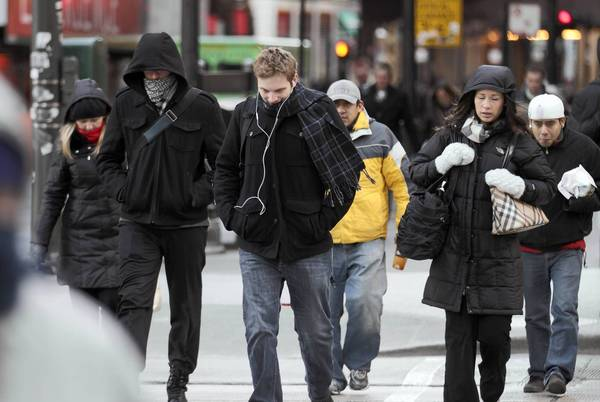 Commuters brace against the cold on Lake Street at Michigan Avenue in downtown Chicago. Wind chill values could reach minus-25 degrees overnight, and the air will be cold enough to cause frostbite in half an hour for exposed skin, according to the weather service.