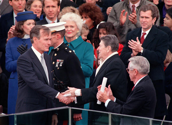 President Ronald Reagan greets newly-inaugurated president George H.W. Bush, with George W. Bush at far right, during Bush's swearing-in ceremony, January 20, 1989, in Washington, DC.