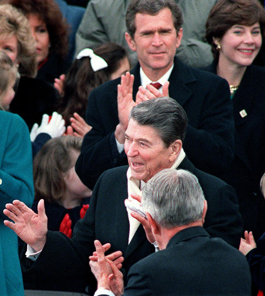 President Ronald Reagan responds to applause in his honor as George W. Bush and Laura Bush (background),  applaud during George Bush, Sr.'s  swearing-in ceremony, January 20, 1989, in Washington, DC..
