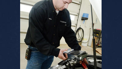 Brandon DeLano, Production Manager for Ron's Collision Center in Somerset, demonstrates the use of a battery tester, one of the most used tools in winter auto upkeep.