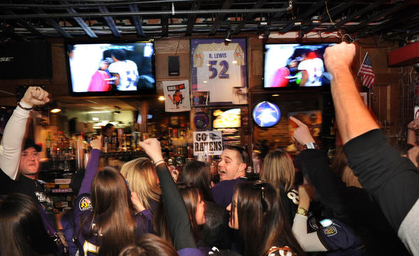 Baltimore Ravens fans cheer the screen in a Federal Hill bar as the Ravens beat the Patriots 28-13