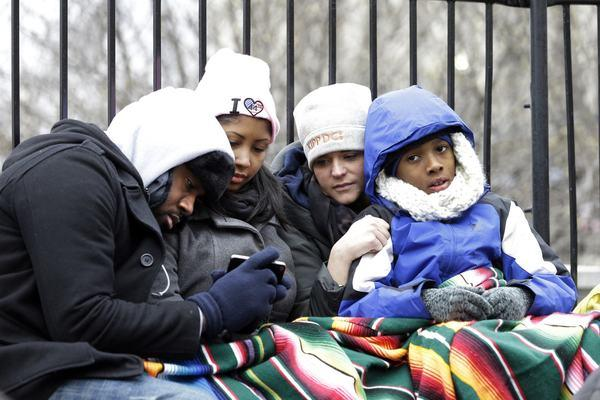 Bundled up against the chill, Augustus Jones, left, Joi Baker, Kristen Conliss and Makhi Inge watch the inaugural ceremonies on a smartphone Monday in Washington.