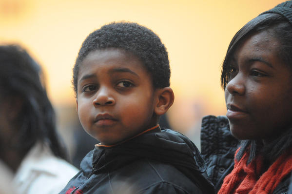 Caleb McKinney, 5, left, and his sister, Dierra McKinney, 18, right, of East Windsor listen to the Lift Every Voice and Sing Gospel Choir during a Martin Luther King Day celebration at The Wadsworth Atheneum Museum of Art in Hartford Monday.
